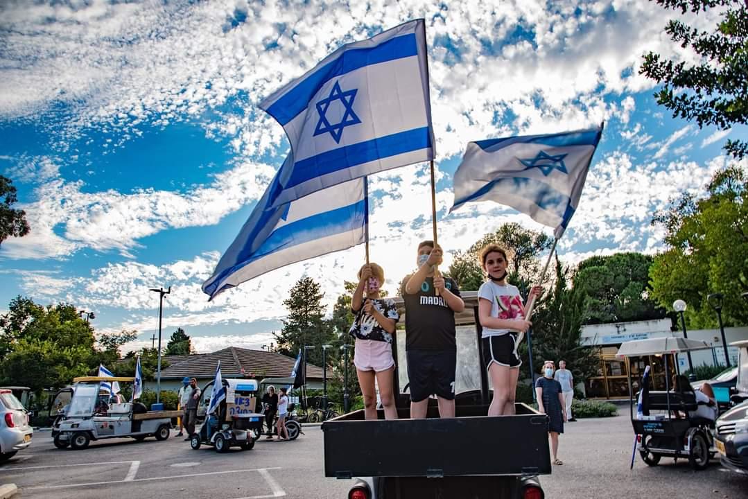 גפן, ישי ולין מעין השופט מניפים בגאווה את דגלי ישראל במחאת הקלנועיות השבוע. צילום: אלכס פינדלינד